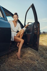 Lady in white tunic getting out of black car