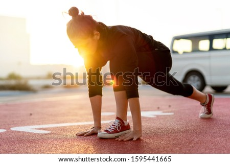 Lady is exercising after jogging on the rubber jogging track
