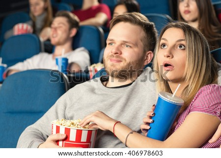 Lady is shocked. Beautiful young couple hugging watching movies together at the cinema