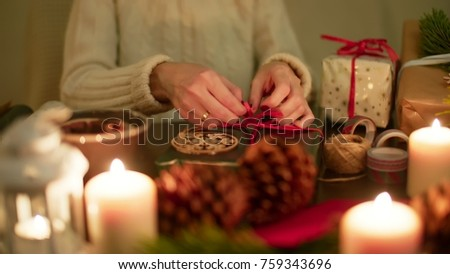 Stock Photo Lady is Wrapping a Christmas Present with Red Ribbon at Decorated Festive Table with Gifts and Candles in the Evening. 4K