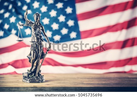 Lady Justice and American flag in the background. #1045735696