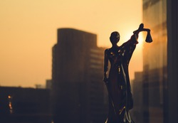 Lady Justice, Law concept. Silhouette of Themis with building background. Statuette of justice. Statuette of the goddess of justice