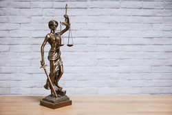 Lady Justice or Justitia the goddess of justice statue on desk - legal law legislation concept - brick wall background with copy space