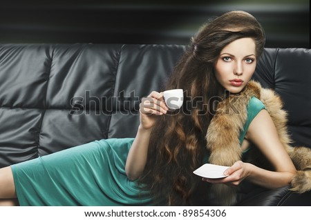 lady laying down on sofa keeping and drinking from a little cup of coffee. wearing green dress. she is lying on the sofa, looks in to the lens and takes a cup hand and saucer with left hand.