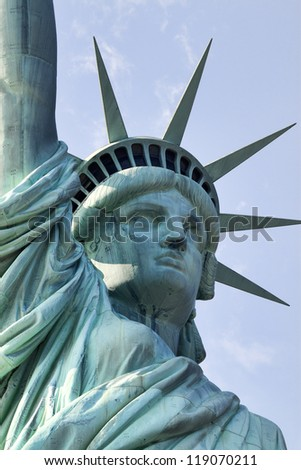 Lady Liberty. Classic close-up image of the upper torso and head of the Statue of Liberty.  The image is shot against a blue sky.