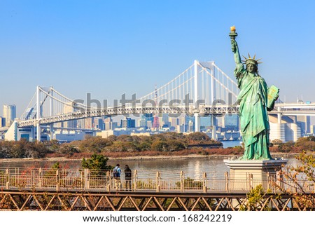 Lady liberty juxtaposed against Rainbow Bridge in Tokyo, Japan.
