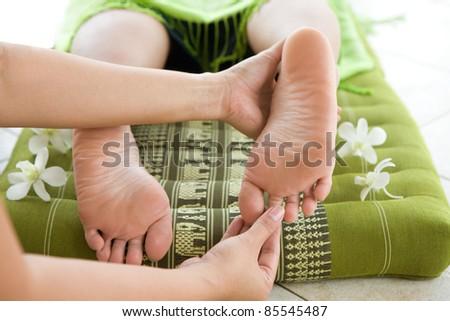 Lady masseur giving female patient a foot reflexology.