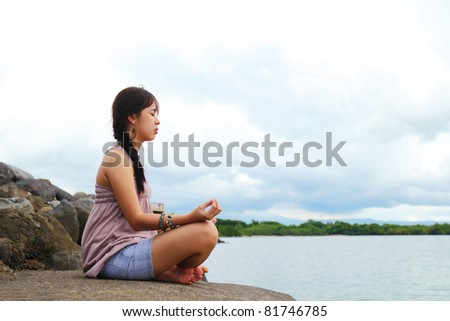 Lady meditating by the sea