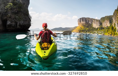 Lady paddling the kayak in the calm tropical bay