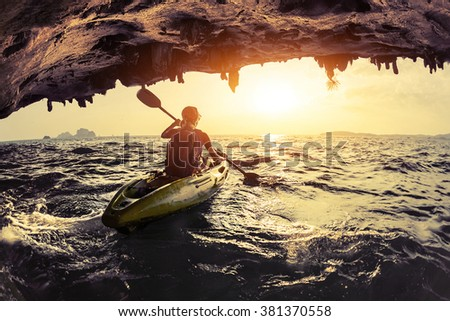 Lady paddling the kayak in the rough sea #381370558