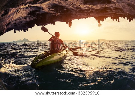 Lady paddling the kayak in the rough sea at sunset #332395910