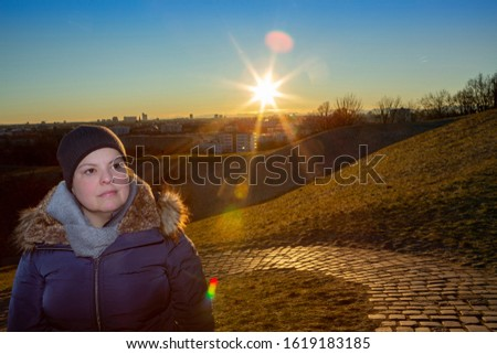 Lady poses for a portrait outdoors. She is outdoors wearing winter clothes.