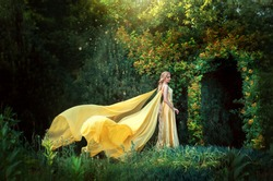 Lady princess stands in fantasy summer forest. arch from natural green leaves tree. Long blond hair.  magic goddess