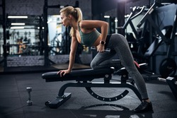 Lady putting one knee on a weights bench with other foot on the ground and raising a dumbbell