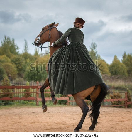 Lady riding a horse in a historical costume of the 19th century