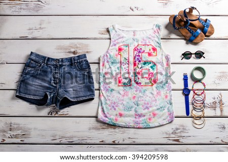 Shutterstock Lady's outfit with jeans shorts. Woodern showcase with female outfit. Casual outfit for teenage girls. Colorful tank top and accessories.