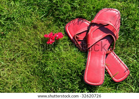 Lady's red slip-on sandals on green grass giving the feeling of barefoot and relaxation in summertime