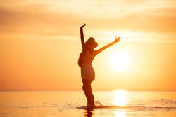 Lady's silhouette stands with raised arms at tranquil sunset beach