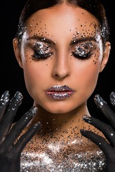 Lady seasoned with shiny sparkles all over her face and on the tips of her fingers. Painted hands with the black paint are near the face. Closed eyes, calm emotion.