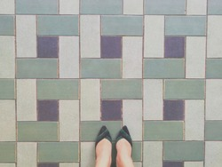 Lady selfie of her feet with green and black shoes on art pattern tiles floor. Business woman. Top view.