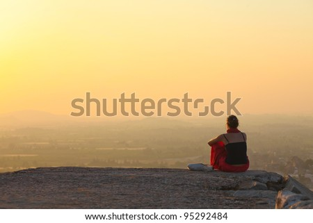 Lady sitting at sunset in Hampi, India