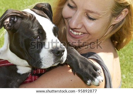 Lady smiles at Pit Bull puppy looking over her shoulder - stock photo