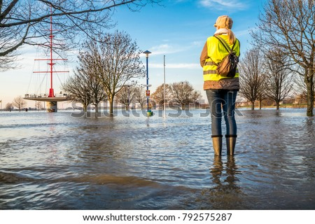 Lady standing in flooded street in wellys #792575287