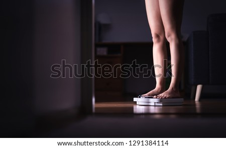 Lady standing on scale. Weight loss and diet concept. Woman weighing herself. Fitness lady dieting. Weightloss and dietetics. Dark late night mood. Negative copy space.