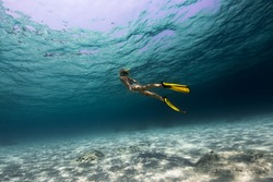 Lady swimming underwater over the sandy bottom in a tropical sea