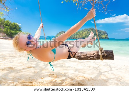 Lady swinging in shade on picture perfect tropical beach with view of island and turquoise coral reef on a sunny summer day.