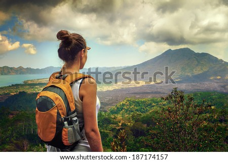 Lady tourist with a backpack standing on top of the mountain and enjoy the beautiful volcano Batur. Indonesia