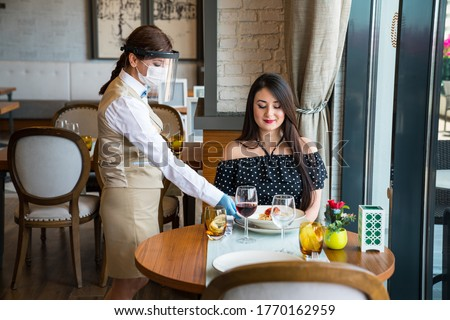Lady Waitress Serving Food In Restaurant. Covid-19 (corona virus, epidemic) for safety, the waiter wears a protective mask and gloves