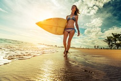 Lady walking with surfboard along the tropical beach