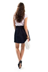 Lady walks and holds handbag. Dark heel shoes with skirt. Clutch bag and gold bracelets. Model in semi formal outfit.