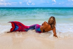 Lady wearing a Mermaid tail laying on a beach in the waves, Boracay Island, Philippines