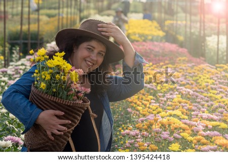 Lady wearing denim shirt holding basket with chrysanthemum flowers and one hand touching cowboy hat that she wears with background of colorful floral farm. Easy to use with copy space to use.  #1395424418