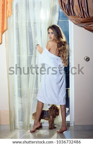 Lady with pensive face in bathrobe with nude shoulders. Girl enjoys morning near window with her cute dog. Sexy nude woman with long hair looks hot and desire. Attraction and desire concept. #1036732486