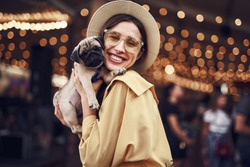 Lady with puppy. Cute pretty young lady wearing stylish hat and smiling while hugging adorable little puppy