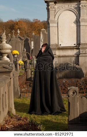 Lady with victorian cape visiting a very old graveyard
