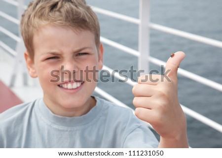Ladybird on little boy big finger show ok on deck of big passenger ship, focus on ladybird