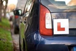 Laerner driver 'L' sign at the back of a blue hatchback compact car
