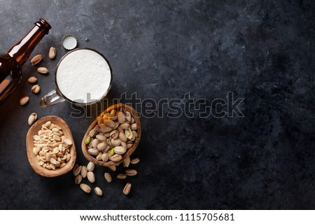 Lager beer and snacks on stone table. Various nuts. Top view with copy space #1115705681