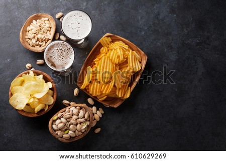 Lager beer glasses and snacks on stone table. Nuts, chips. Top view with copyspace