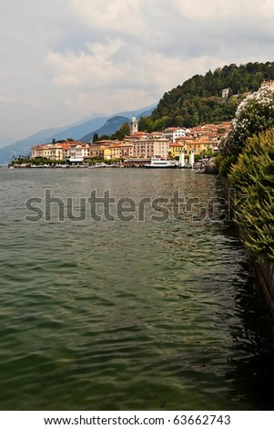 Lago di Como coastline town with mountains in background at summer.