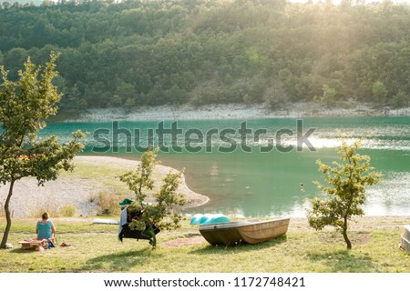 Lago di Fiastra, Macerata, Le Marche, Italy: View Of The Lake With A Boat and A Person Gazing and Sun Light