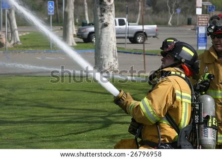 LAGUNA BEACH, CA - FEB 19: Firefighter recruit sprays water during fire fighting drills at the local Fire Department training area on February 19, 2009 in Laguna Beach, California.