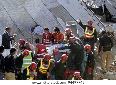 LAHORE, PAKISTAN - FEB 06: Rescue workers shift dead body of a victim towards ambulance during rescue operation at the site of building collapse incident on February 06, 2012 in Lahore.