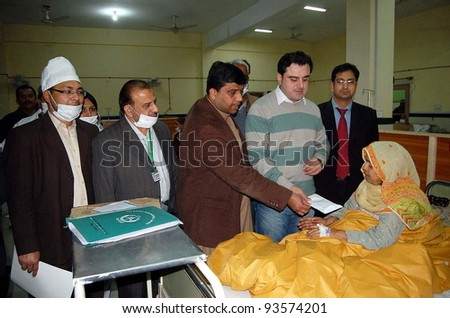 LAHORE, PAKISTAN - JAN 25: MNA Bilal Yaseen and MPA Ajasim Sharif give thirty-thousand rupees to a cardiac patient during their visit at Ganga Ram hospital on January 25, 2012 in Lahore.