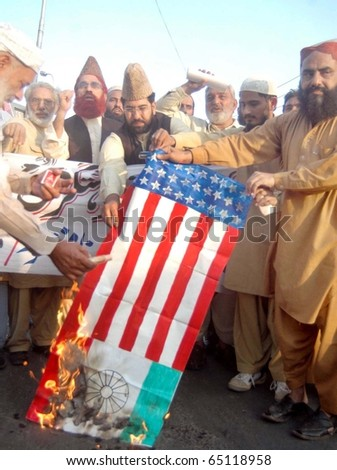 LAHORE, PAKISTAN - NOV 14: Activists of World Pasban Khatam-e-Nabouat burn US and India flag during against India and US Governments during a protest demonstration on November 14, 2010 in Lahore.