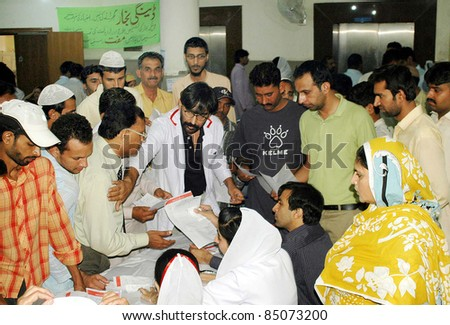 LAHORE, PAKISTAN - SEPT 20: People gather at a counter established for Dengue Virus patients at Ganga Ram hospital on September 20, 2011Lahore.
